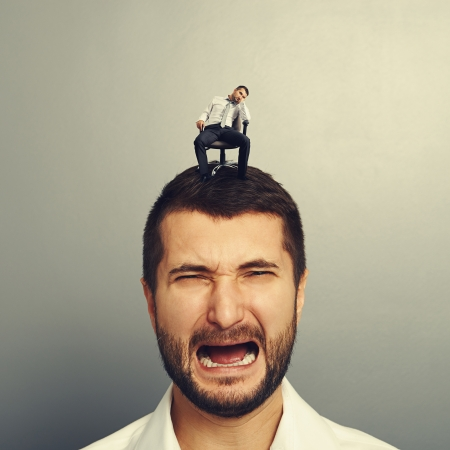 portrait of sad screaming man with small bored man on the head Stock Photo