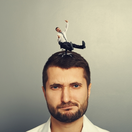 discredit: small joyful man rolling on the head big dissatisfied man