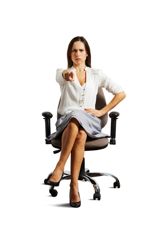 strict: strict businesswoman pointing at camera over white background Stock Photo