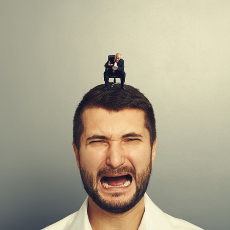 discredit: small angry boss screaming at big crying man over grey background