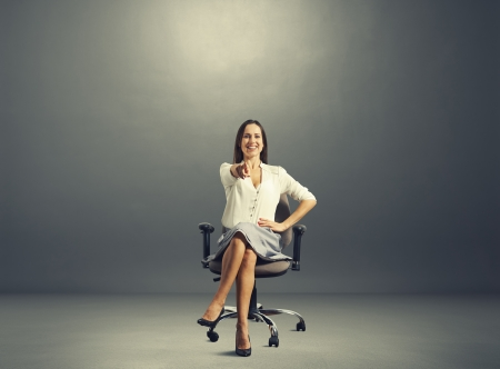 attractive young woman sitting on the office chair and pointing at something photo