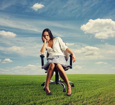 alicaído: Empresaria triste que se sienta en la silla de la oficina en el exterior