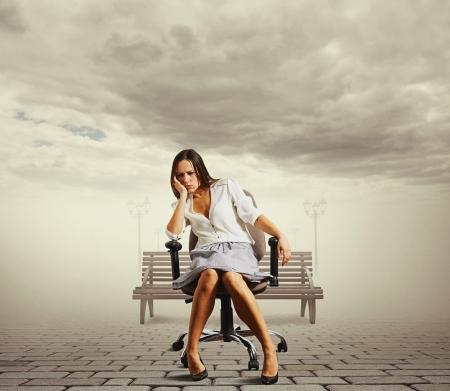 alicaído: mujer joven cansada que se sienta en la silla de la oficina en el exterior