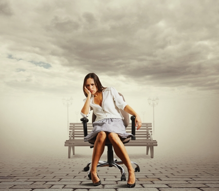 tiresome: tired young woman sitting on the office chair at outdoor  Stock Photo