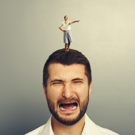 discontented: small leading woman standing on the discontented man and pointing at something Stock Photo