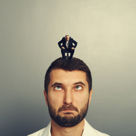 discredit: small angry boss looking at big stupid man over grey background Stock Photo