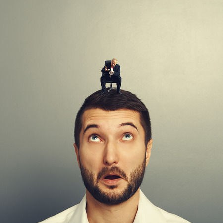 discredit: amazed businessman looking at small senior boss