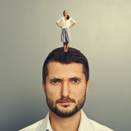 displeased: happy small woman standing on the head of displeased man