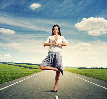 rest in peace: attractive young woman in yoga pose standing on the road