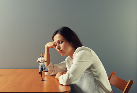 sorrowful businesswoman looking at small meditation woman Stock Photo