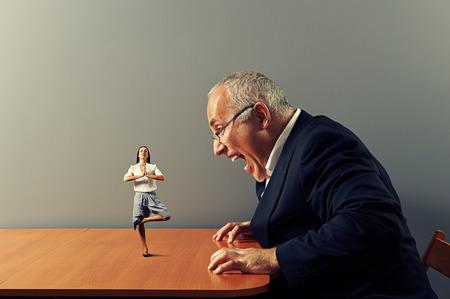 agressieve zakenman schreeuwen op kleine rustige vrouw op de tafel Stockfoto