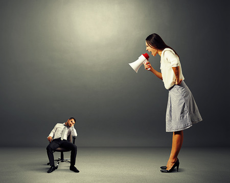 reproach: angry young woman screaming at small lazy man