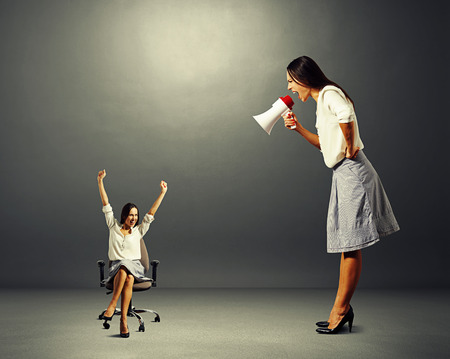 reproach: big woman screaming at small woman on the office chair over dark background Stock Photo