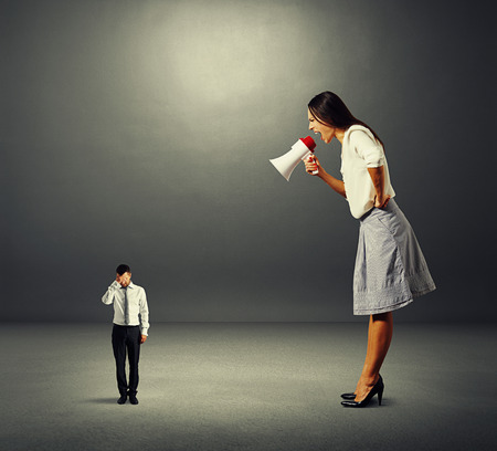 discontented: discontented businesswoman screaming at small stressed businessman over dark background