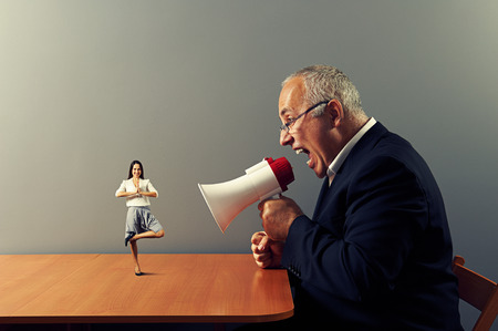 aggressive businessman screaming at small smiley woman on the table photo