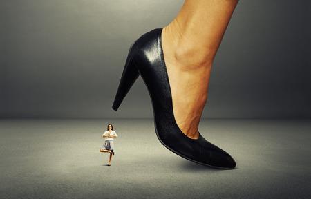 downtrodden: calm smiley businesswoman under big heel over dark background Stock Photo