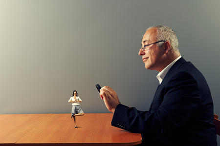 small table: smiley man looking with magnifying glass at small meditation woman on the table