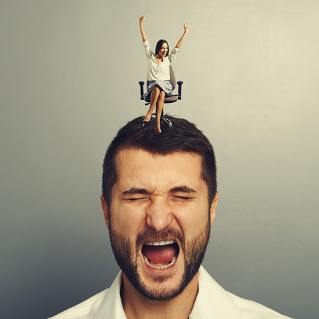 henpecked: stressed man with happy woman on the head over dark background Stock Photo