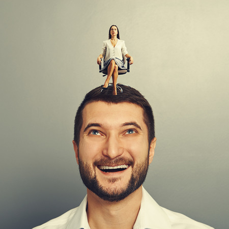 henpecked: excited man looking at strict woman on his head over grey background Stock Photo