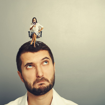henpecked: strict small woman sitting on the displeased man over grey background Stock Photo