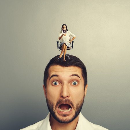 henpecked: startled man with small angry woman on the head Stock Photo