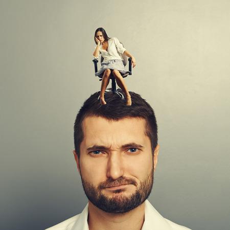 sorrowful: sorrowful woman sitting on the displeased man over grey background