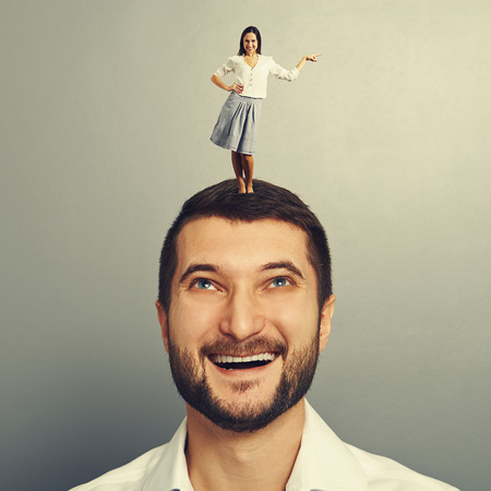 henpecked: happy woman standing on the smiley man and pointing at something over grey background