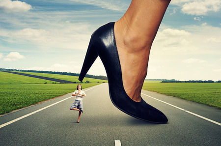 downtrodden: calm yoga businesswoman standing under big heel at outdoor