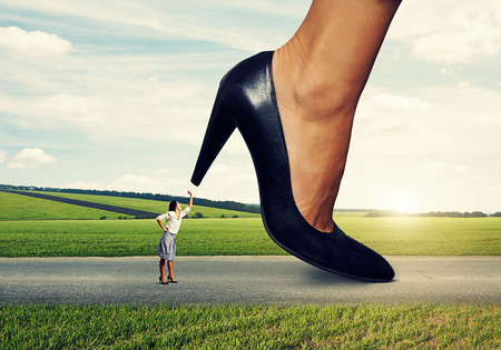 downtrodden: angry woman showing fist and screaming at boss on the road Stock Photo