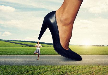 small calm woman under big female heel Stock Photo