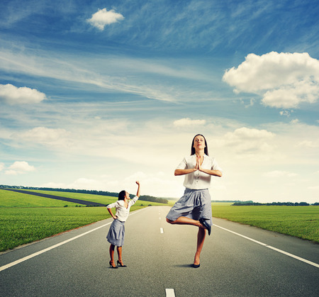 reproach: emotional small woman and calm big woman standing on the road