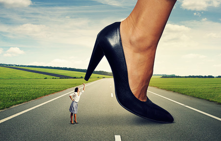 downtrodden: angry woman showing fist and screaming at big lady boss on the road