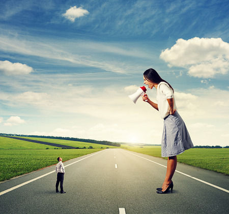 henpecked: emotional big woman with megaphone and small man on the road