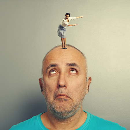 misunderstanding: senior man looking with misunderstanding at excited woman on his head Stock Photo
