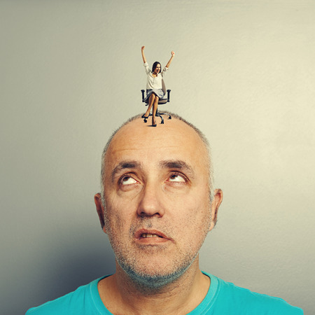 henpecked: displeased man looking at happy young woman on his head