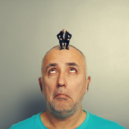 tedious: amazed man looking with misunderstanding at small businessman on his head