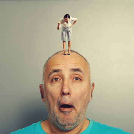 henpecked: amazed man with angry wife on his head