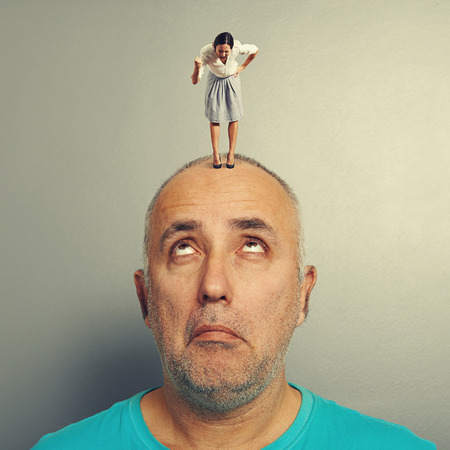 henpecked: surprised man with small angry businesswoman on his head
