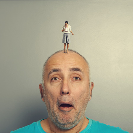 amazed man with small angry woman on his head photo