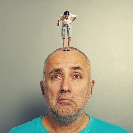 henpecked: sad man with small angry businesswoman on his head