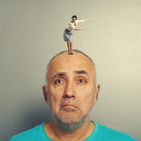 henpecked: sad man with small excited businesswoman on his head over grey background