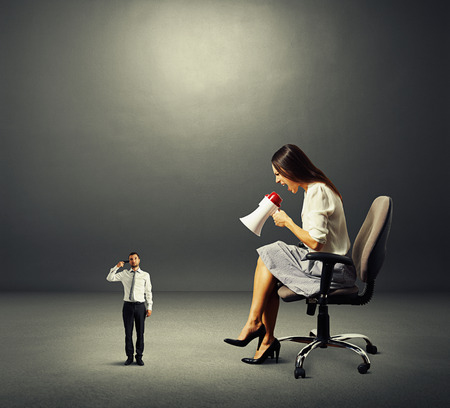 dissatisfied businesswoman and small man with gun over dark background Stock Photo - 27075180