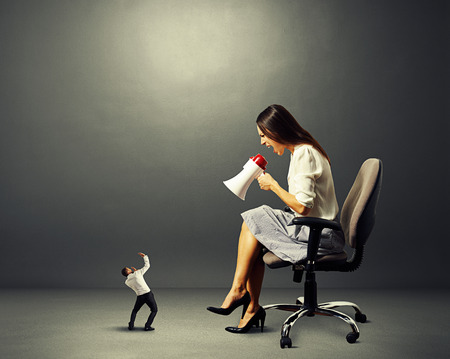 henpecked: aggressive businesswoman and small startled man over dark background Stock Photo