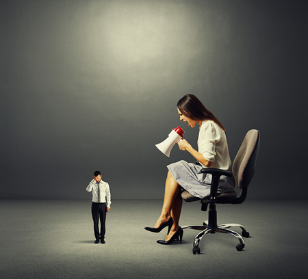 dissatisfied businesswoman and small stressed man over dark background Stock Photo