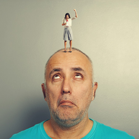 henpecked: amazed man with small aggressive woman on his head over grey background Stock Photo