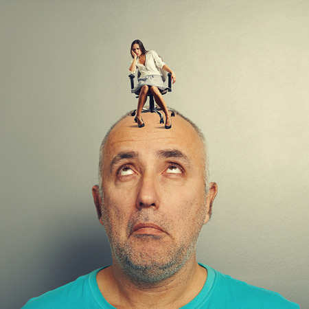 tedious: amazed man with small tired woman over grey background Stock Photo