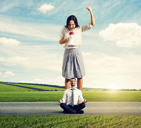 woman shouting: angry woman and calm yoga man on the road Stock Photo