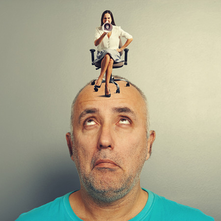 amazed man with small angry woman on his head over grey background photo