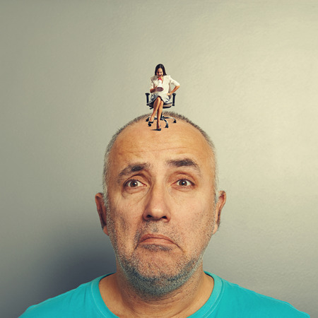 henpecked: sad man and small angry businesswoman on his head over grey background