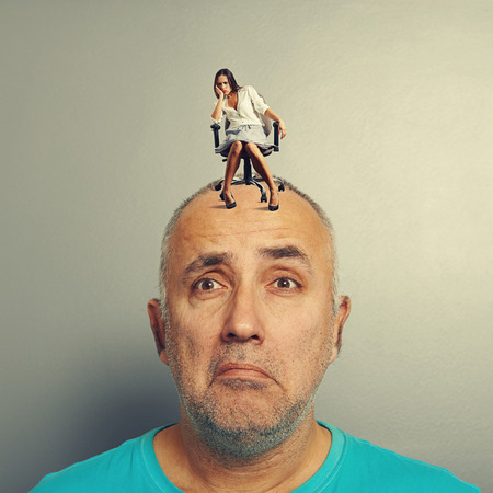 tedious: sad man and small despondent woman on his head over grey background